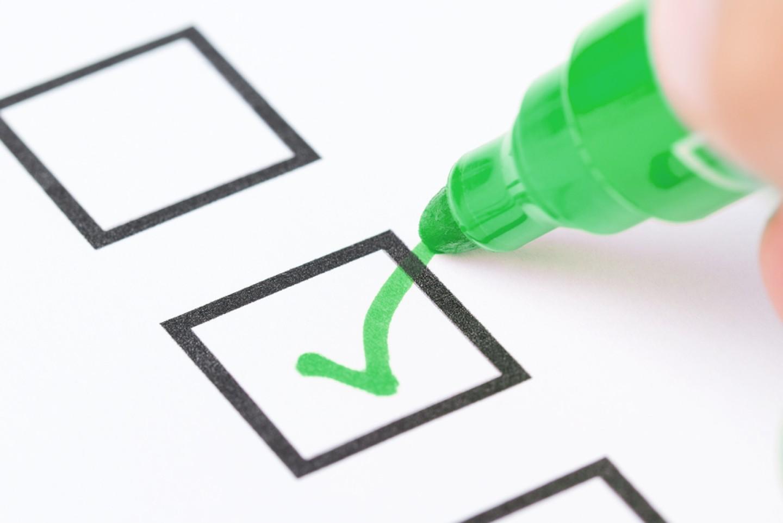 Macro shot of human hand drawing green check mark in checklist b